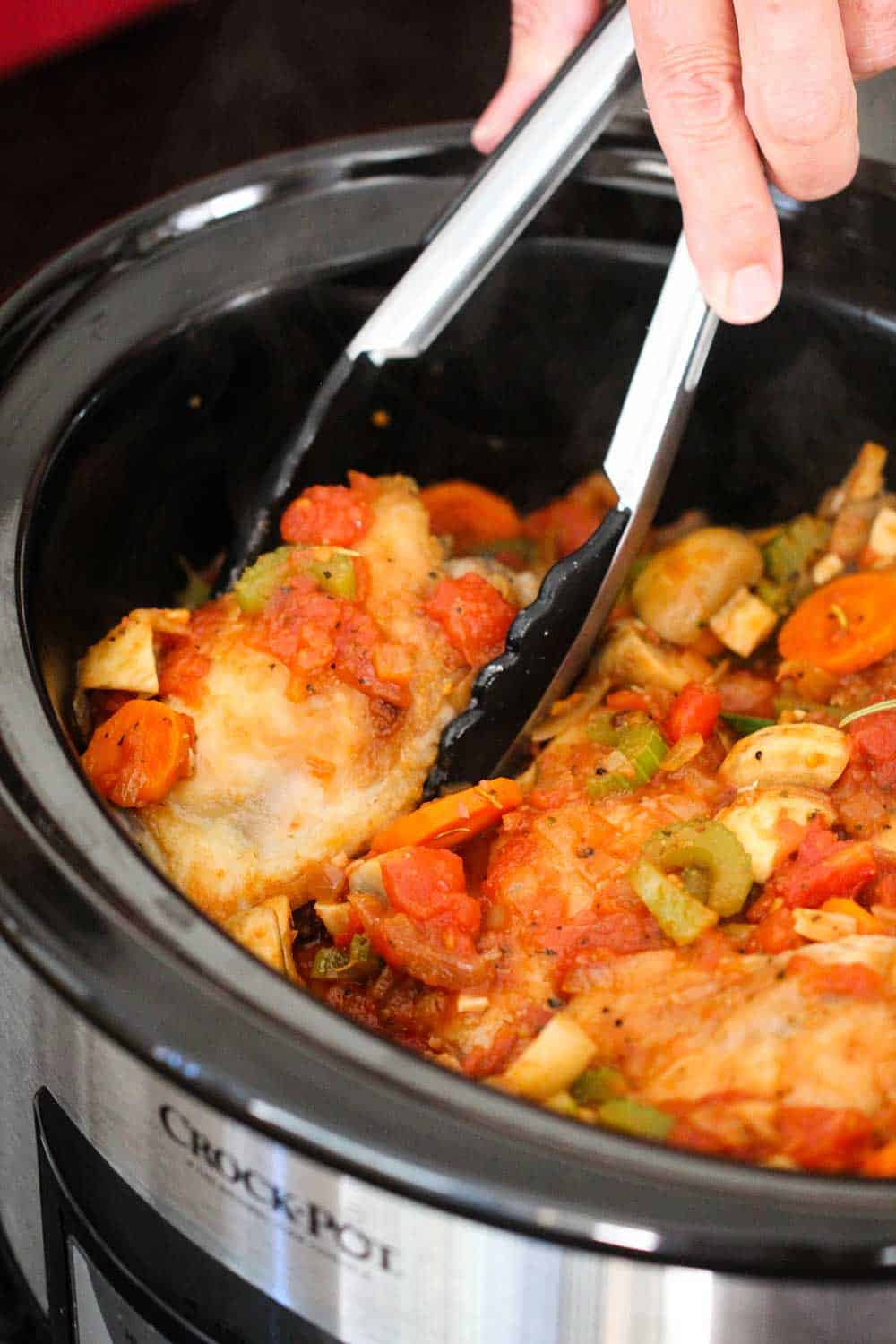 A pair of tongs nestling seared chicken thighs into a stew sauce in a crock-pot for Provençal chicken stew.