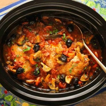 An overhead view of Provençal Chicken Stew in a large black slow cookers.