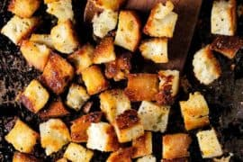 A scraped baking sheet with homemade croutons on it and a wooden spoon.