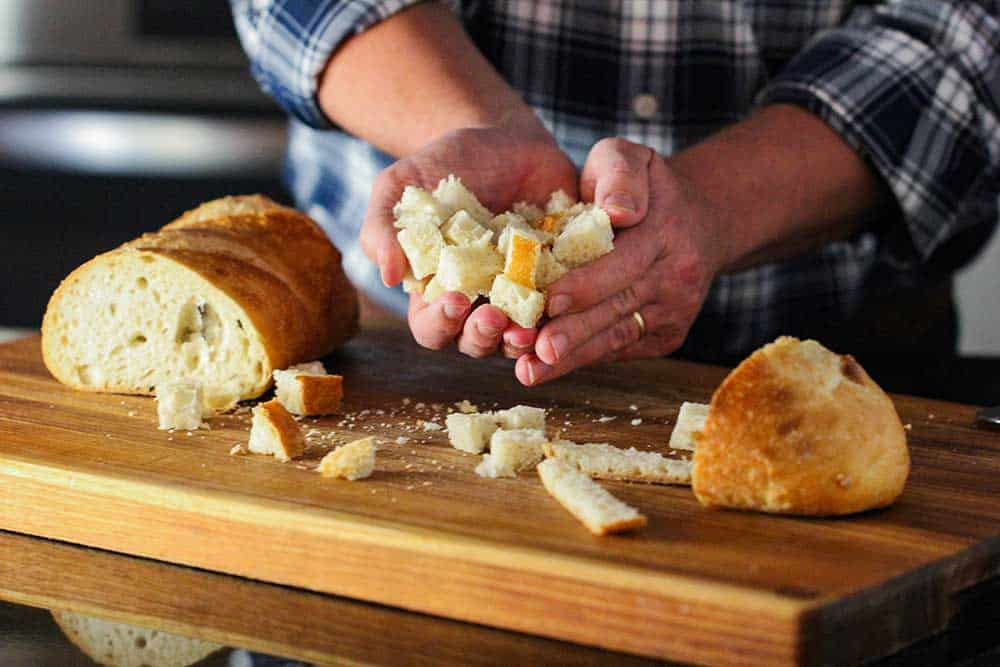 Two hands holding cubes of bread for homemade croutons.