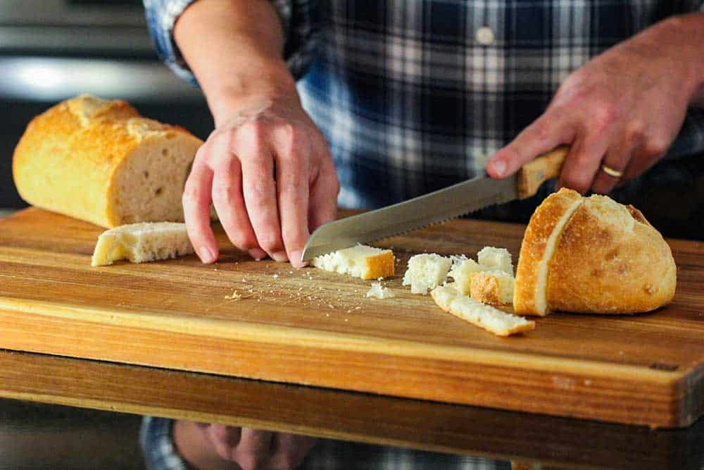 Two hands using a serrated knife to cut strips of bread on a cutting board.