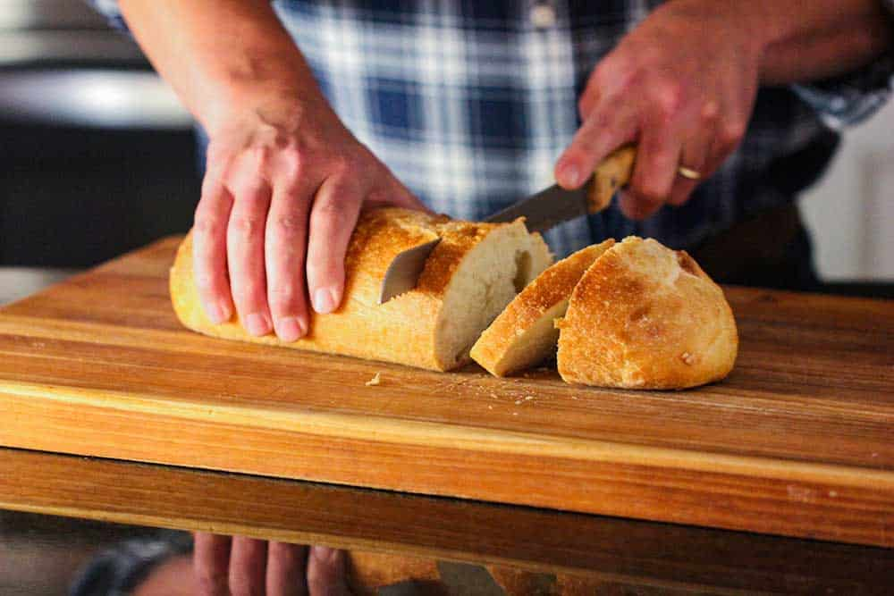 Two hands slicing through a loaf of Italian bread on a large wooden cutting board.