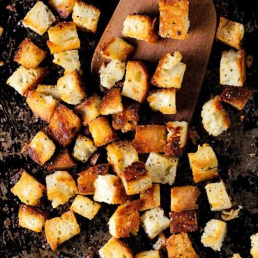 homemade croutons on a scraped black baking sheet with a wooden spoon.