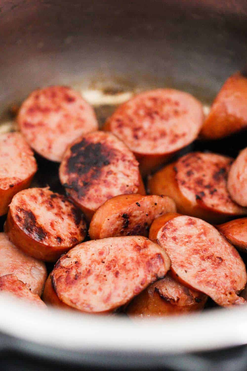 A large pot of sliced and seared smoked sausage pieces for smoked sausage stew.