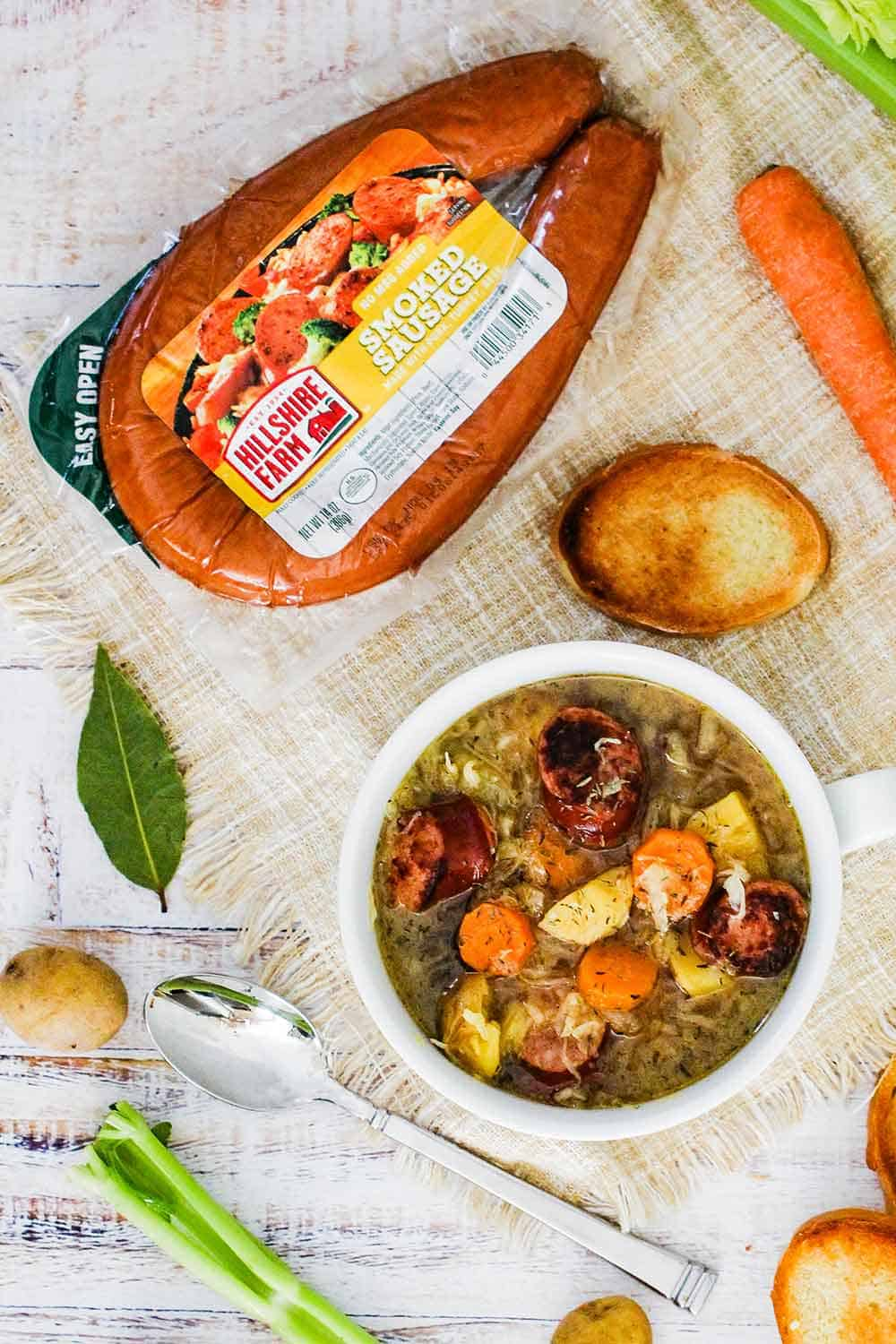 An overhead view of a package of smoked sausage next to a bowl of smoked sausage stew surrounded by vegetables on a white board.