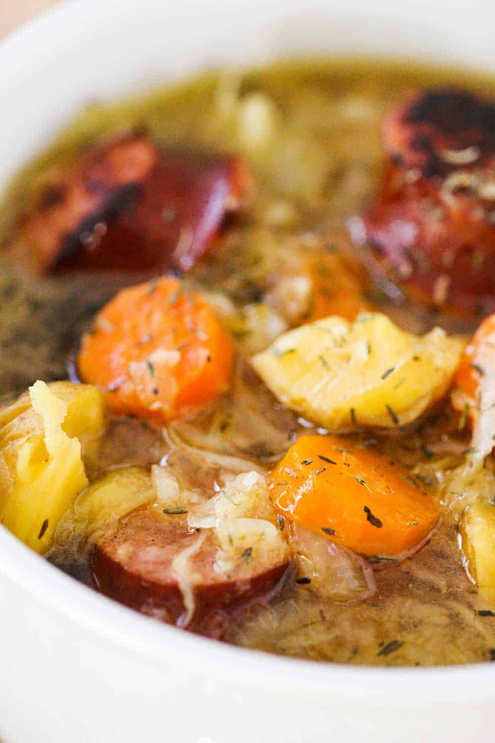 A close up view of a bowl full of stew with sausage, potatoes and carrots.