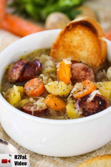 A large white bowl filled with smoked sausage stew and a piece of toasted bread stuck in the side with carrots in the background.