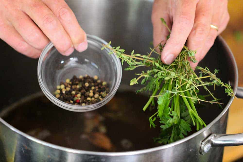 Two hands holding a small bowl of peppercorns and a bunch of herbs over a large stock pan for roasted chicken stock.