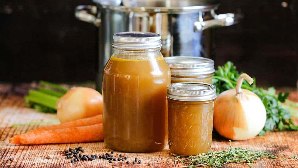 Three varied-sized jars holding roasted chicken stock in front of a large stock pan next to vegetables and herbs.