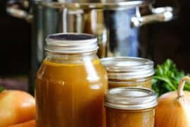 Three jars filled with roasted chicken stock with a stock pot and vegetables around them.