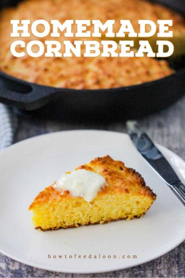A slice of homemade cornbread on a white plate with a pad of butter on top.