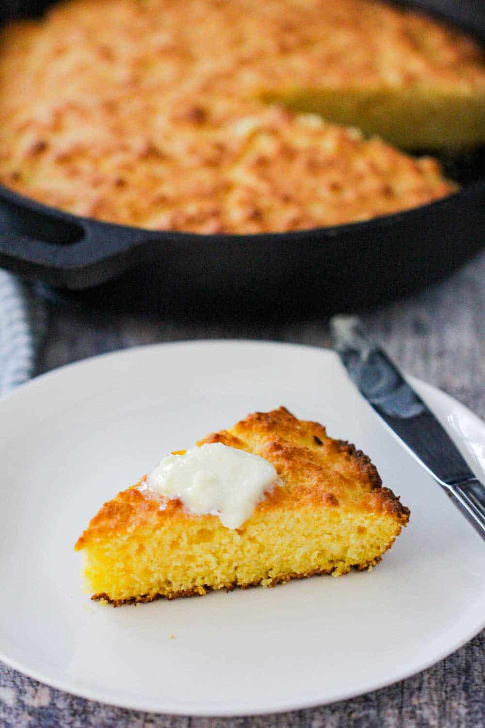A slice of homemade cornbread with a pad of butter on top next to a skillet of cornbread.
