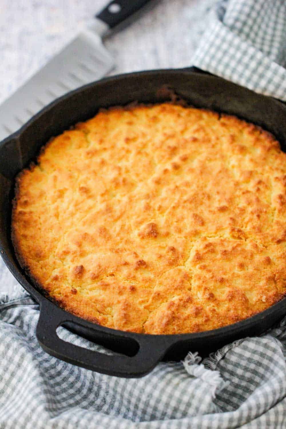 Homemade cornbread in a cast iron skillet with two patterned napkins nearby.
