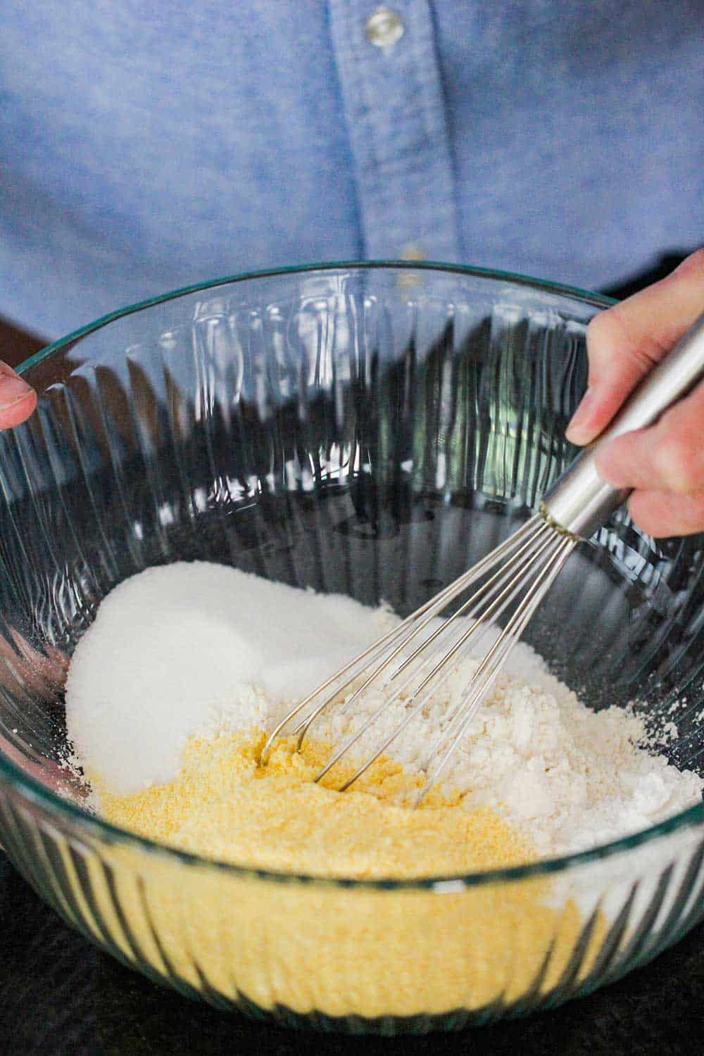 A hand using a whisk to combine cornmeal, flour, salt and baking powder in a large glass bowl.
