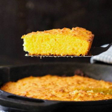 A slice of homemade cornbread being raised out of a skillet with a spatula.