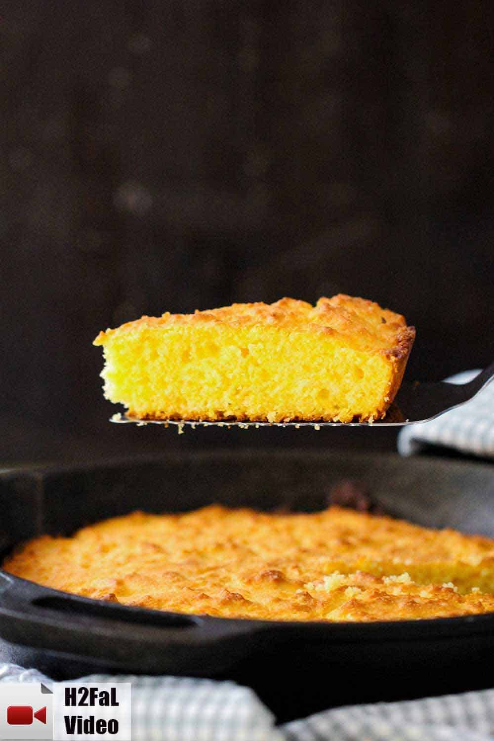 A spatula rising out of a cast iron skillet of homemade cornbread.