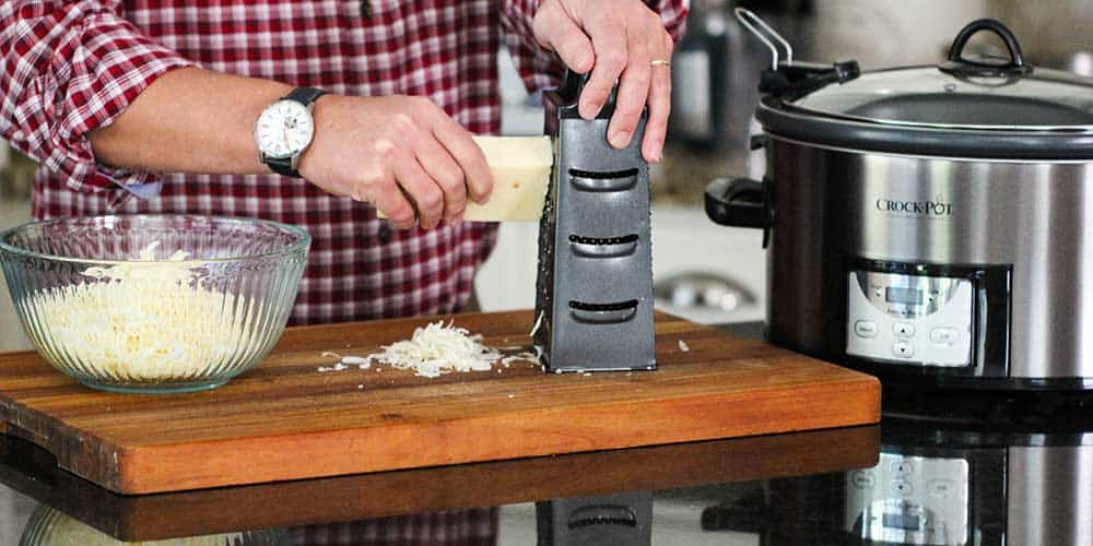 A hand grating a block of Swiss cheese on a box grater.