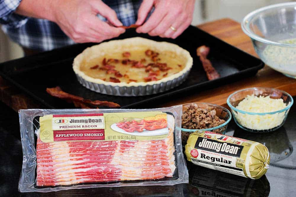 Two hands crumbling bacon into a tart pan lined with dough with bowls of cooked sausage nearby.