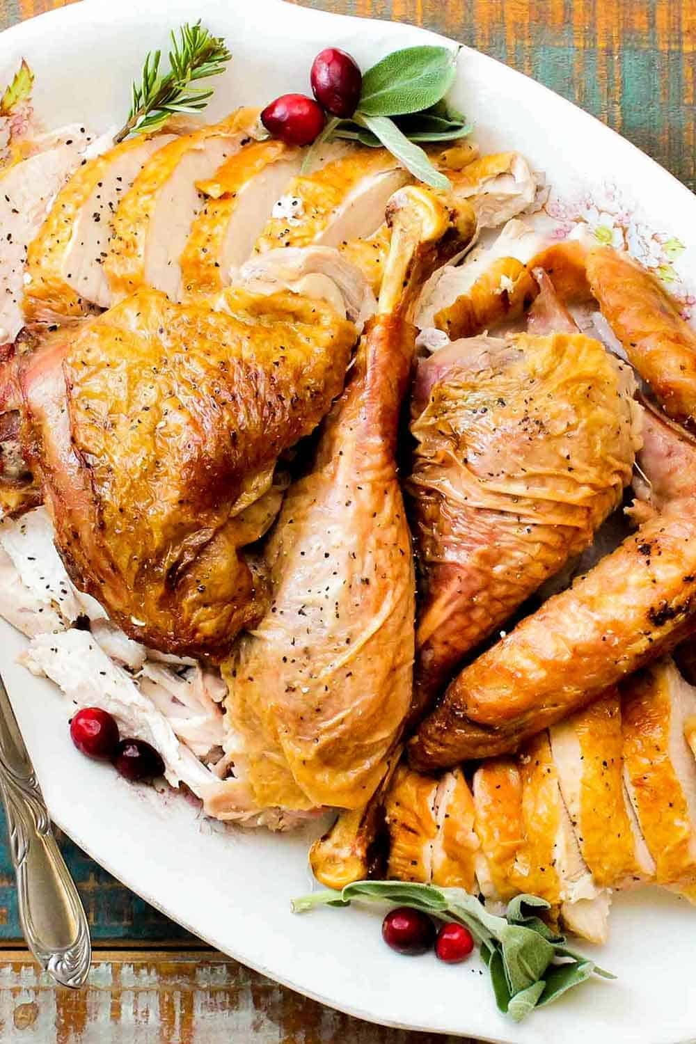 A large white platter of cooked and carved spatchcocked turkey with cranberries next to it.
