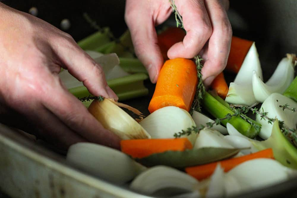 Two hands placing cut carrots, celery and onion in a large roasting pan.