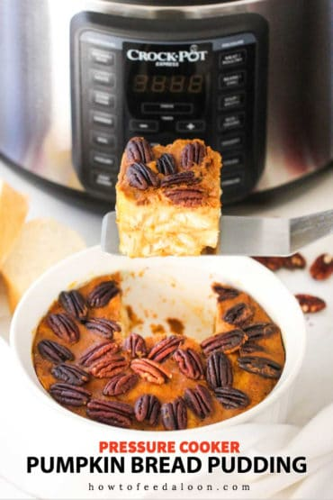 A slice of pumpkin bread pudding being lifted out of a dish in front of a pressure cooker.