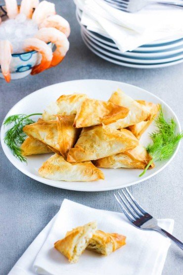 A white plate holding air fryer phyllo triangles next to shrimp cocktail.