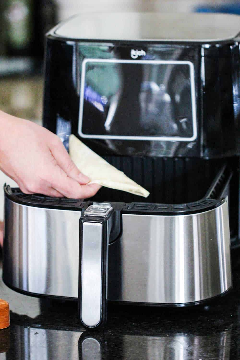 A hand lowering a phyllo triangle into an air fryer basket.