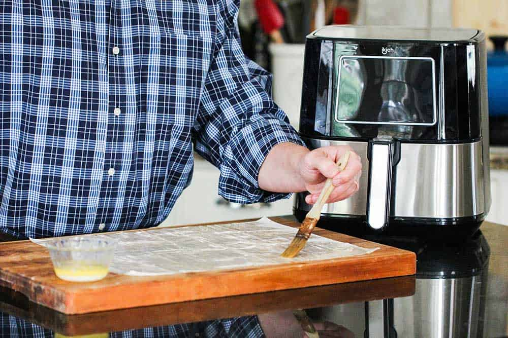 A hand using a brush to apply melted butter onto phyllo dough next to an air fryer.