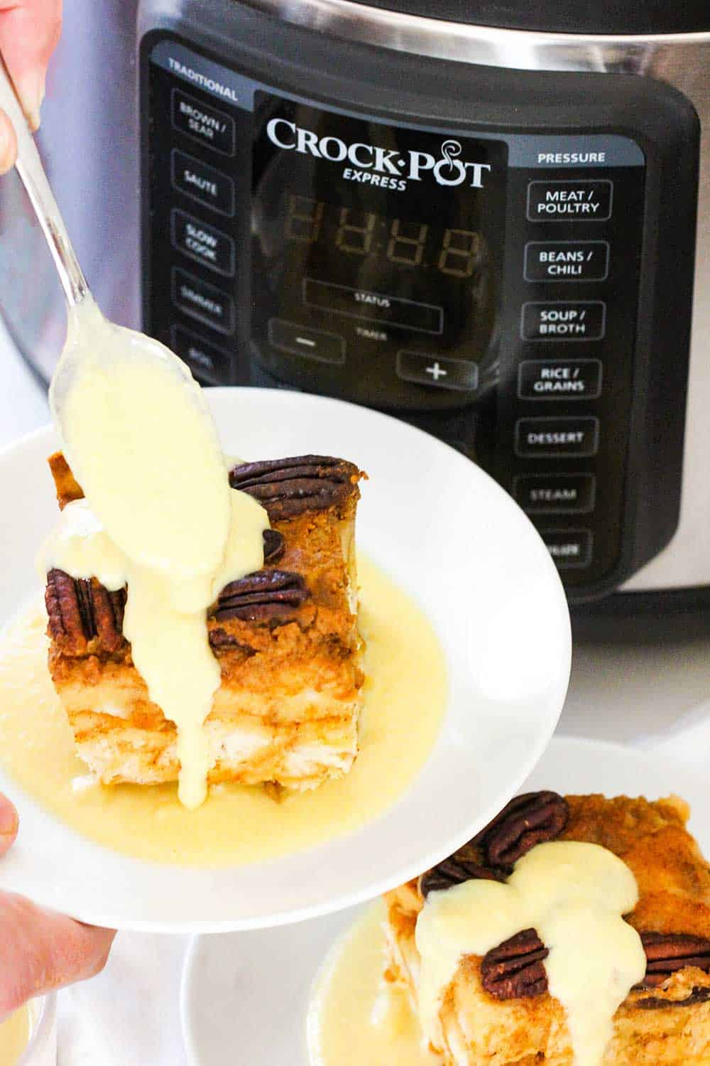 A spoon pouring custard onto a plate of pumpkin bread pudding next to a pressure cooker.