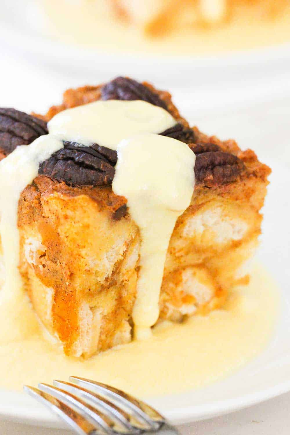 A plate of pressure cooker pumpkin bread pudding with vanilla custard sauce drizzled on top.