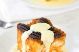 A piece of pumpkin bread pudding with vanilla custard poured over the top on a white plate.