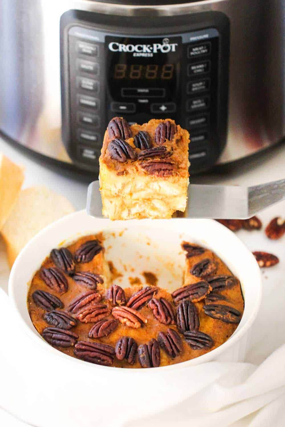 A slice of pumpkin bread pudding being held up on a spatula next to a Crock Pot Pressure Cooker.