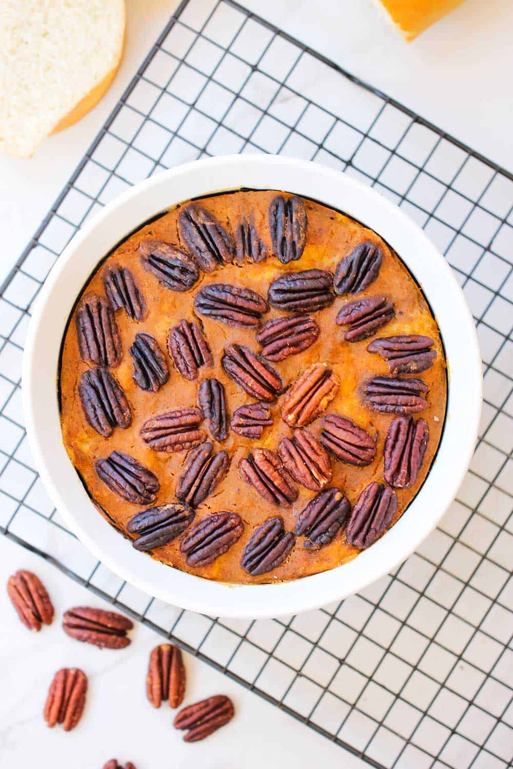 A bowl of pressure cooker pumpkin bread pudding on a baking rack next to pecans.