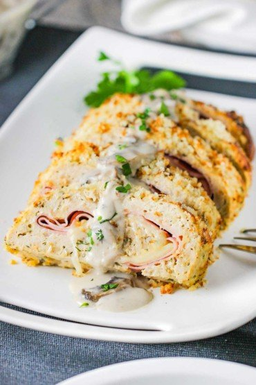 A white platter holding sliced cordon bleu meat loaf with a mushroom gravy drizzled over the top.