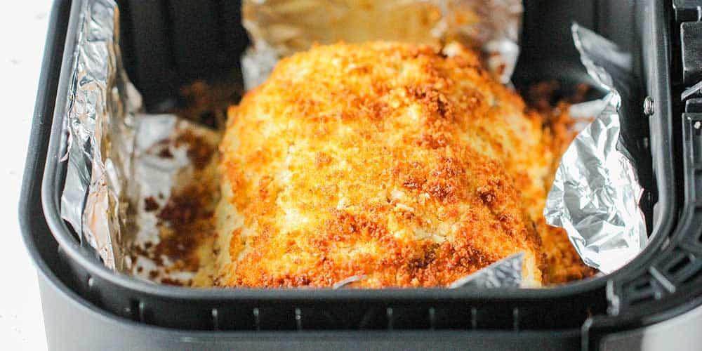 A golden loaf of cordon bleu in the basket of an air fryer.