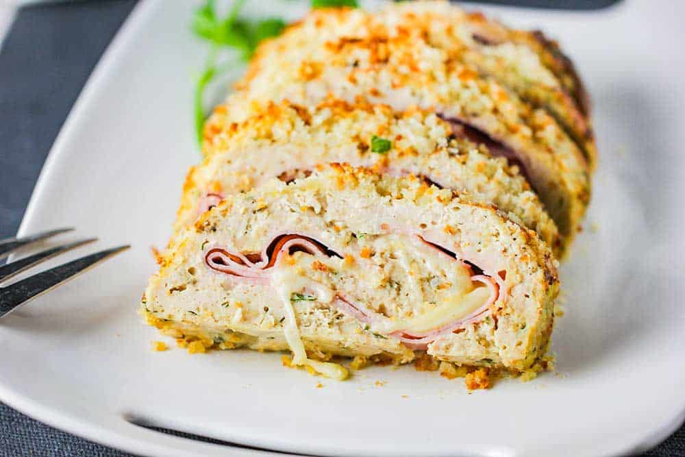 A white platter holding sliced air fryer cordon bleu meatloaf on it with a fork nearby.
