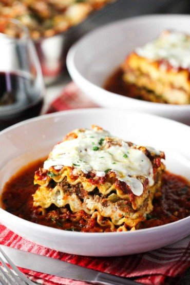 A white bowl holding classic meat lasagna with another bowl behind it next to a glass of red wine.