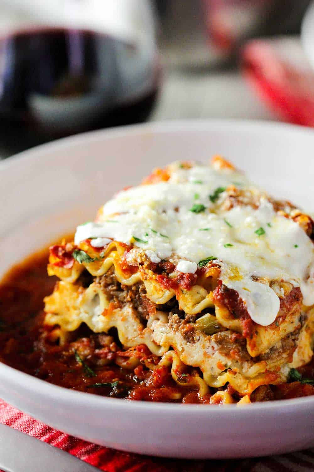 A white bowl of classic meat lasagna next to a glass of red wine.