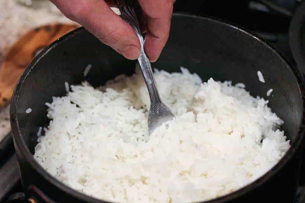 A hand fluffing perfect steamed rice in a pan to fluff the rice.