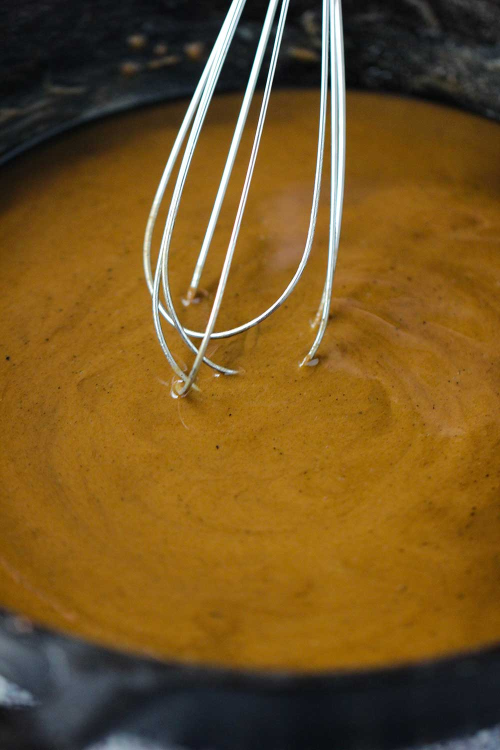 A brown roux being stirred with a whisk in a black cast-iron skillet.