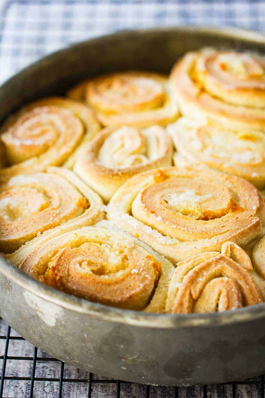 A circular metal pan holding freshly baked orange sweet rolls.