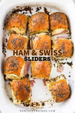 An overhead view of a white baking dish filled with ham and Swiss sliders with one missing.