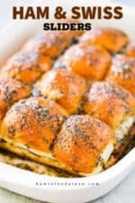 A white baking dish filled with baked ham and Swiss sliders.
