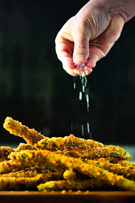 A hand sprinkling coarse sea salt of a pile of fried asparagus.