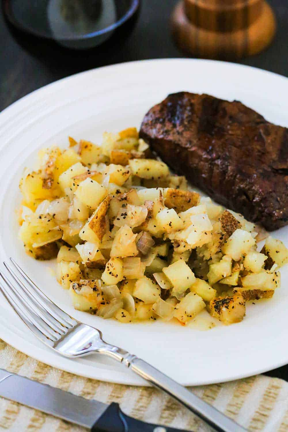 A white dinner plate loaded with roasted potatoes and a grilled steak with a fork nearby.