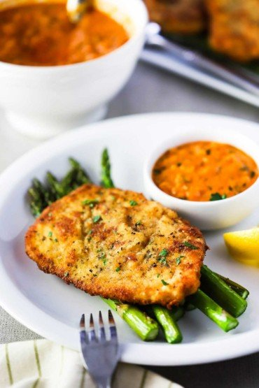 A white dinner plate filled with roasted asparagus topped with Parmesan crusted chicken with a small bowl of vodka sauce next to it.