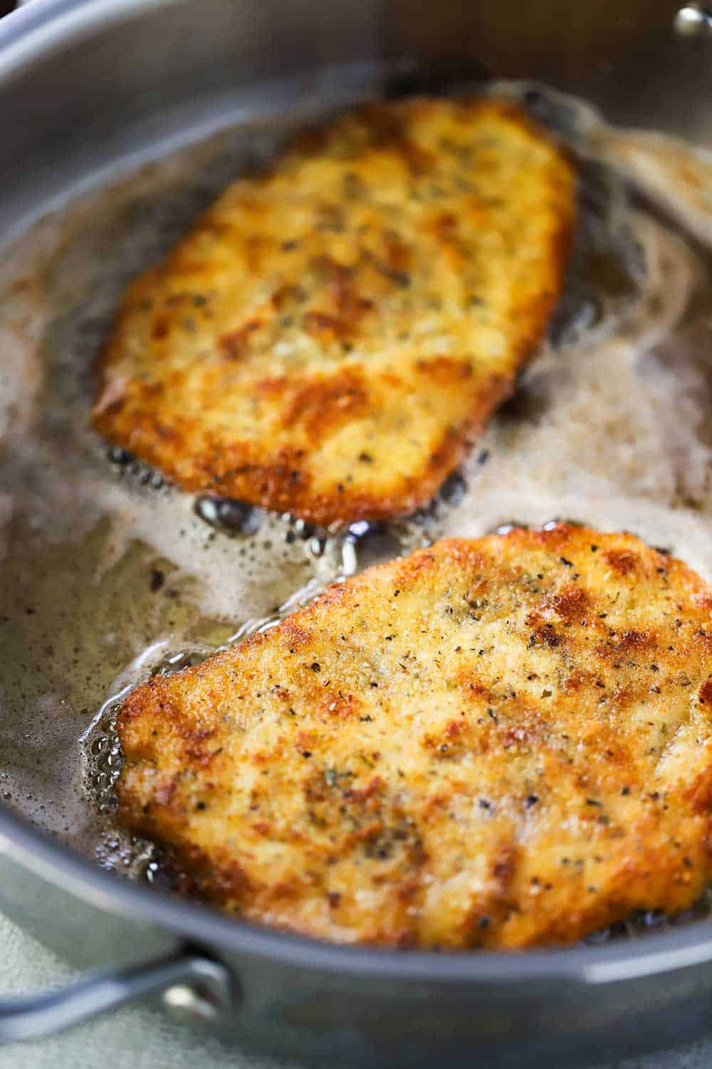 Two Parmesan chicken cutlets cooking in butter in a later steel skillet.
