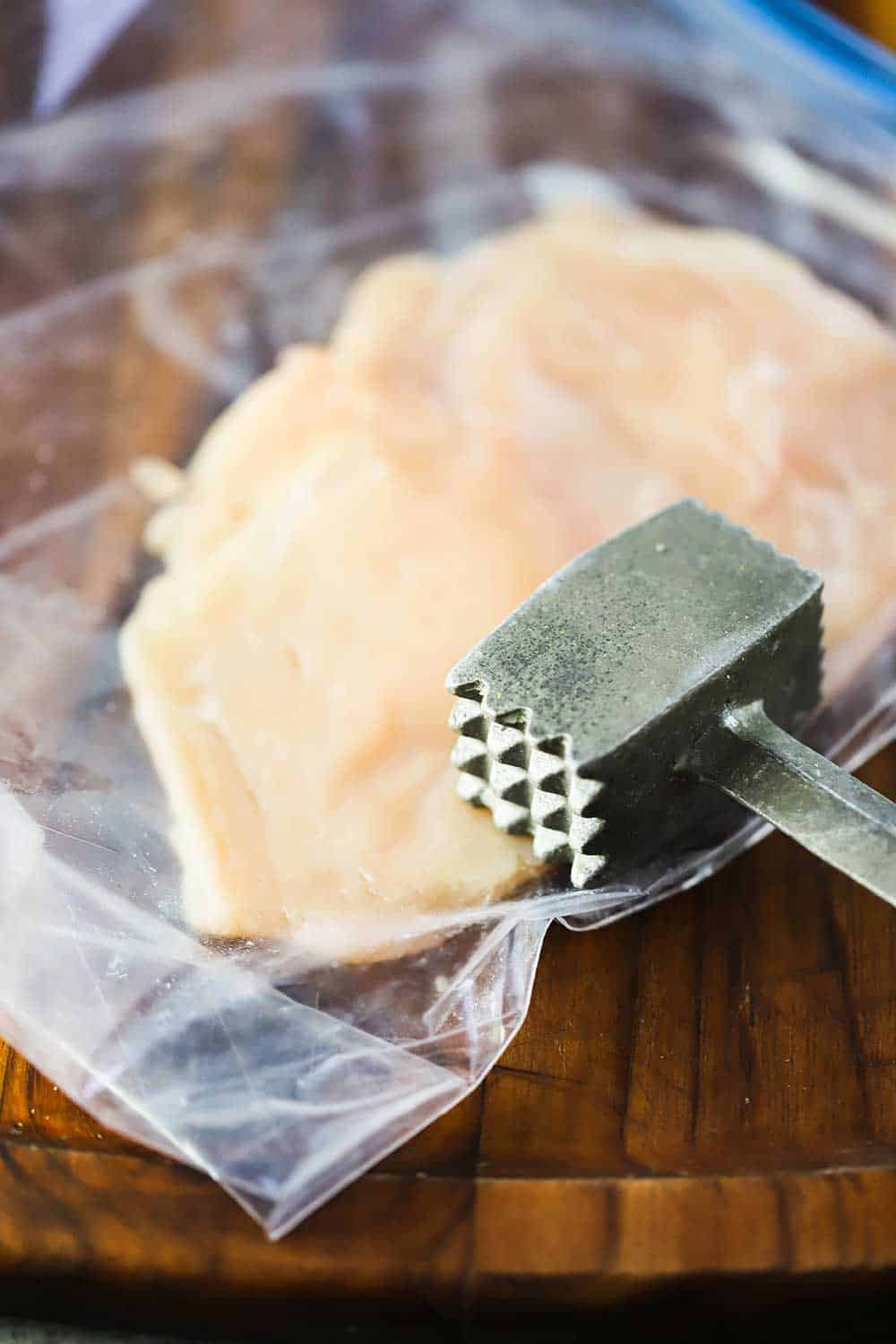 A mallet turned on its side on a chicken breast in plastic freezer baggie.
