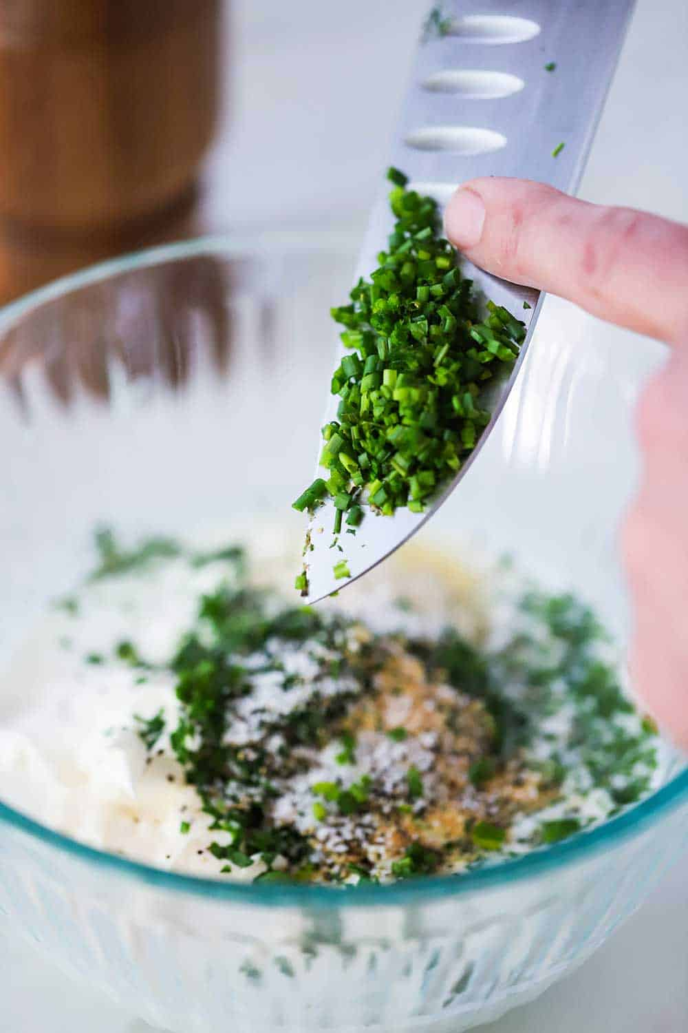 A hand scraping chopped chives into a bowl of Ranch dressing ingredients.