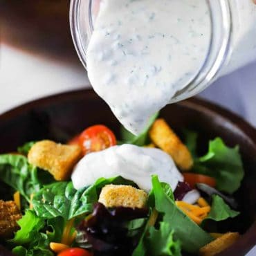 A hand pouring homemade ranch dressing onto a green salad in a brown wooden bowl.